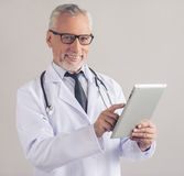 Handsome mature doctor. Handsome mature medical doctor in white coat and eyeglasses is using a digital tablet, looking at camera and smiling, on gray background Stock Photos