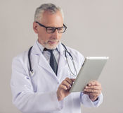 Handsome mature doctor. Handsome mature medical doctor in white coat and eyeglasses is using a digital tablet and smiling, on gray background Stock Photos