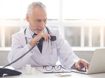 Handsome mature doctor Stock Photos