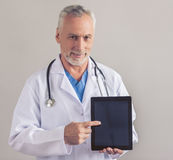 Handsome mature doctor. Handsome mature medical doctor in white medical coat is holding a digital tablet, looking at camera and smiling, on gray background Stock Photography