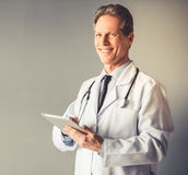 Handsome mature doctor. In white coat is holding a digital tablet, looking at camera and smiling, on gray background Royalty Free Stock Photo