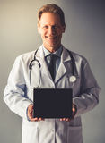 Handsome mature doctor. In white coat is holding a digital tablet, looking at camera and smiling, on gray background Royalty Free Stock Images
