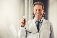 Handsome mature doctor. In white coat is holding a stethoscope, looking at camera and smiling while standing in hospital corridor Stock Photography