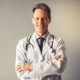 Handsome mature doctor. In white coat is looking at camera and smiling while standing with crossed arms on gray background Stock Images