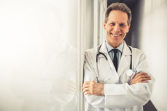 Handsome mature doctor. In white coat is looking at camera and smiling while standing with crossed arms in hospital corridor Stock Photo