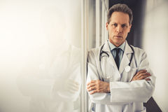 Handsome mature doctor. In white coat is looking at camera while standing with crossed arms in hospital corridor Stock Images