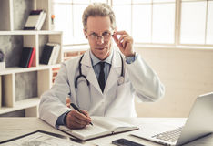 Handsome mature doctor. In white coat is making notes and looking at camera from under eyeglasses while working in office Royalty Free Stock Image