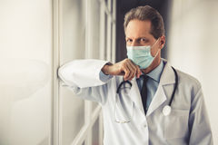 Handsome mature doctor. In white coat and procedure mask is looking at camera while standing in hospital corridor Royalty Free Stock Images