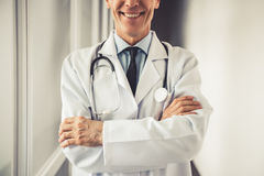 Handsome mature doctor. In white coat is smiling while standing with crossed arms in hospital corridor Royalty Free Stock Photography