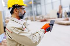 Handsome mature engineer in the factory. With digital tablet Royalty Free Stock Photos