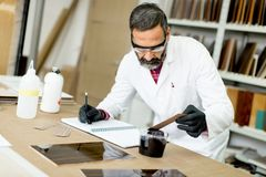 Handsome mature engineer working in laboratory in the furniture Royalty Free Stock Photography