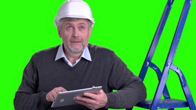 Handsome mature foreman using digital tablet. Mature supervisor in white helmet working on computer tablet, chroma key background stock video