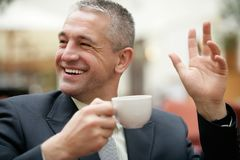 Gray-haired senior businessman drinking cup of coffee stock photography