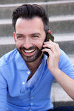 Handsome mature guy talking on mobile phone. Close up portrait of handsome mature guy sitting outdoors and talking on mobile phone Stock Images