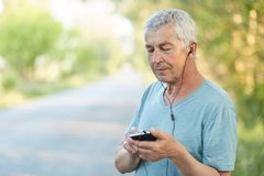 Handsome mature male with grey hair, holds smart phone, listens music in playlist, enjoys fresh air in rural area, dressed in casu Stock Photos