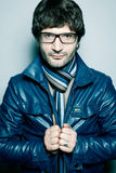Handsome mature man in blue jacket and glasses. Eyewear concept. Portrait of a fashionable handsome mature man in trendy glasses, blue jacket with striped scarf Stock Image