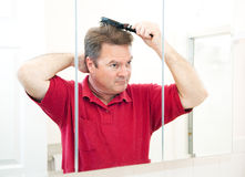 Handsome Mature Man Brushing His Hair. Handsome mature man in his bathroom brushing his hair in the mirror royalty free stock photos