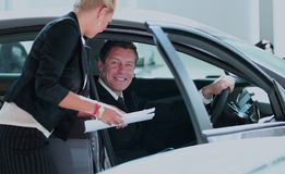 Handsome mature man buying a car at dealership. Handsome successful men buying a car at dealership Stock Photography