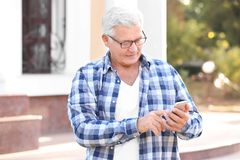 Handsome mature man with cell phone. Outdoors Royalty Free Stock Photography