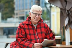 Handsome mature man with coffee and newspaper Royalty Free Stock Photos