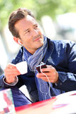 Handsome mature man with cup of coffee and phone Stock Images