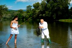 Handsome mature man fishing with young woman in white dress. Man with fishing rod and net. Happy bearded fisher in water