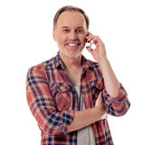 Handsome mature man with gadget. Handsome mature man in casual clothes is talking on the mobile phone, looking at camera and smiling, isolated on white royalty free stock image