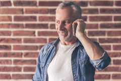 Handsome mature man with gadget. Handsome mature man is talking in the mobile phone and smiling, on brick wall background royalty free stock image