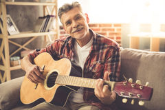 Handsome mature man with guitar. Handsome mature man in casual clothes is looking at camera and smiling while playing guitar at home stock photos