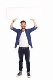 Handsome mature man holding blank billboard over white background. Full length portrait of handsome mature man holding blank billboard over white background stock image