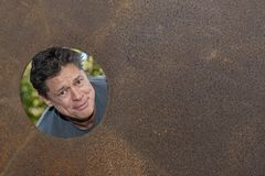 Handsome mature man in the iron plate hole, looking away, grins, happy, contented. Handsome mature man in the iron plate hole, looking away, grins, happy stock photography