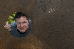 Handsome mature man in the iron plate hole, looking away, grins, happy, contented. Handsome mature man in the iron plate hole, looking away, grins, happy stock image