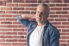 Handsome mature man. Is looking away and smiling, on brick wall background stock photos