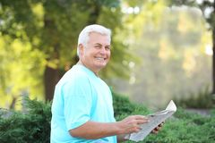 Handsome mature man with newspaper. In park stock photos