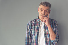 Handsome mature man. Handsome pensive mature man in casual wear is looking at camera, on gray background stock images