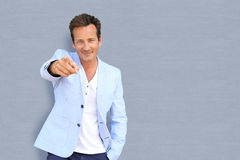 Handsome mature man pointing finger towards camera. Mature man on grey background pointing at camera stock photo