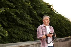 Handsome mature man with professional camera outdoors. Space for text stock images