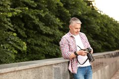 Handsome mature man with professional camera outdoors. Space for text stock image