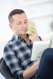 Handsome mature man reading book and eating apple Royalty Free Stock Photography