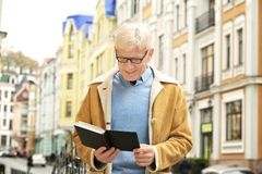 Handsome mature man reading book. Outdoors Royalty Free Stock Photo