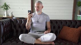Handsome mature man sitting on the couch at home and communicating with somebody through video chat on his smartphone