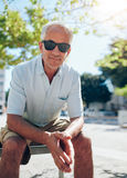 Handsome mature man sitting outdoors in the city Stock Photos