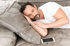 Handsome mature man sleeping. On a couch with blank screen mobile phone Stock Photo