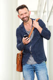 Handsome mature man standing outdoors with mobile phone. Portrait of handsome mature man standing outdoors with mobile phone and smiling royalty free stock photography