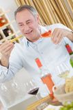 Handsome mature man tasting glass rose wine stock images