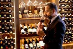 Handsome mature man tasting red wine Stock Photo