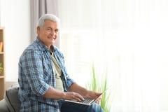 Handsome mature man using laptop stock photos