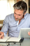 Handsome mature man using tablet and working. Handsome guy working from home with electronic tablet Royalty Free Stock Image