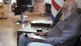 Handsome mature man wait his turn in barbershop. Senior man reads magazine and looks around him. Gray-haired man smiles and winks to camera. Prores codec stock footage