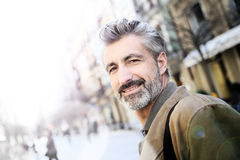 Handsome mature man walking in the streets stock photo
